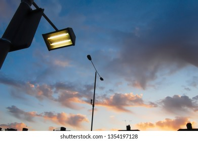 Road sign lamp pictured against dramatic sunset sky in mellow suburbia. Copy space.