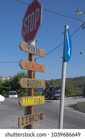 Road sign with names of settlements in the Greek language and the direction of the movement on the island Rhodes and Stop sign (Greece).