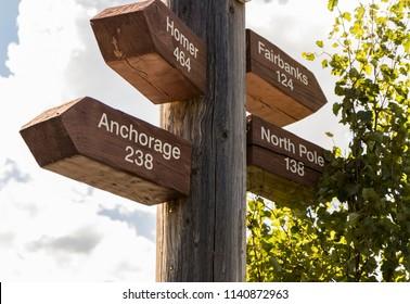 Road sign at Nenana River near Denali National Park, Alaska, USA. Mileage to Anchorage, Fairbanks, North Pole, and  Homer.