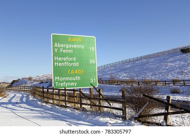 Road sign on the A465 with directional and milage information to Abergavenny, Hereford and Monmouth in winter with snowy conditions and blue sky background.