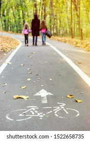 Road sign on asphalt for the ride cyclists and Family (mother and two daughters) walking on a bicycle path in autumn park