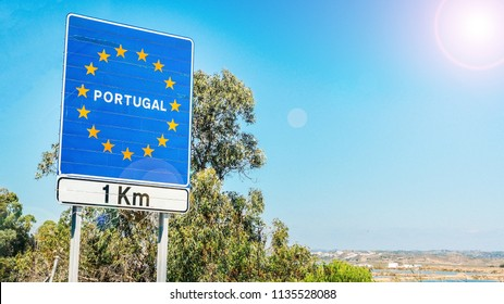 Road sign on the border of a European Union country, Portugal 1km ahead with blue sky copy space. Crossing over on highway from Spain.