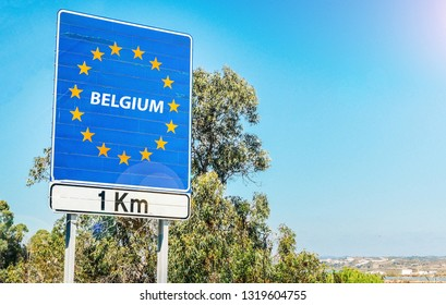 Road sign on the border of a European Union country, Belgium 1km ahead with blue sky copy space