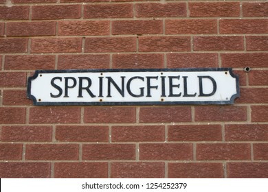 "Road Sign on a brick wall reading  ""Springfield."""