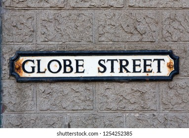 "Road Sign on a brick wall reading  ""Globe Street."""
