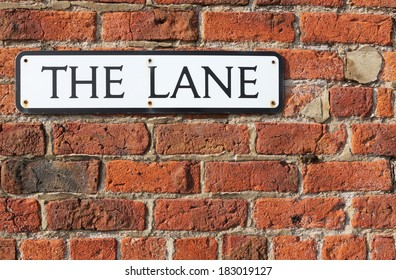 """Road Sign on a brick wall reading  """"The Lane."""""""