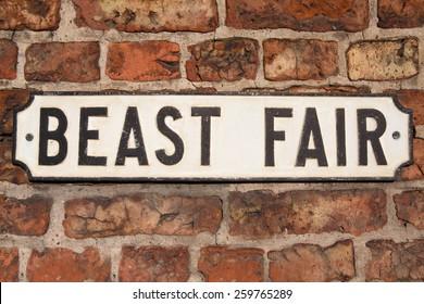 "Road Sign on a brick wall reading ""Beast Fair."""