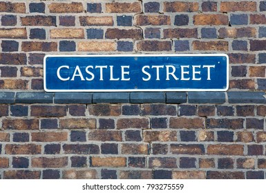 """Road Sign on a brick wall reading """"Castle Street"""" in Warwick, Warwickshire, UK."""