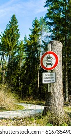"""A road sign on a dirt road through a pine forest, featuring pictures of a car and motorbike and text reading, """"Forestry Vehicles Only"""" in German."""