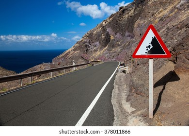 road sign on a street: rock fall