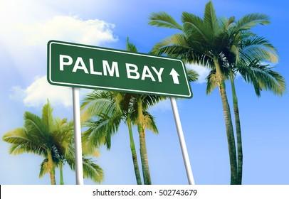 Road sign - Palm Bay. Green road sign (signpost) on blue sky background. (3D-Illustration)