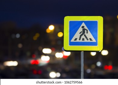 road sign pedestrian crossing on the night on the back lights of cars. Night road.