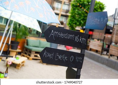 Road Sign pointing to Amsterdam and cold beer (koud bier in dutch) on a terrace in the city of Tilburg. the Netherlands. Relax on the background.