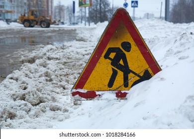 Road sign signaling repair work standing in the snow