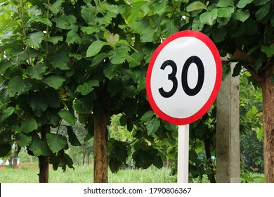 Road sign speed limit, 30 mph, on a road. Transportation and sign concept.