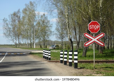 Road sign STOP on suburban non regulated empty one way railroad crossing on asphalted road view from car, beautiful European railway landscape at Sunny summer day on blue sky and birch tree background