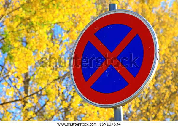 Road sign STOPPING and autumn trees