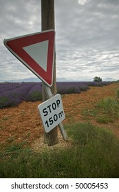 Road sign tied to a power pole warns drivers of an upcoming stop in the countryside. Lavender fields are in the background, and the sky overhead is overcast. Vertical shot.