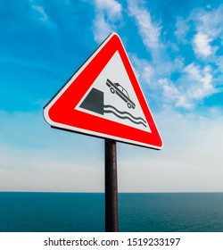 Road sign warning about dangerous way along the sea coast. Car falling down from the cliff to the water.