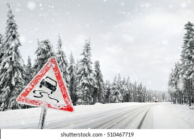 Road sign warning against slippery road due to snow ice