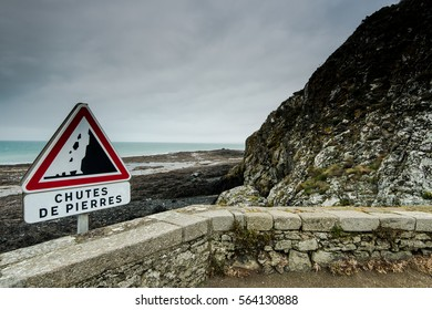 Road sign warning of danger cliffs in France on the edge of coast.