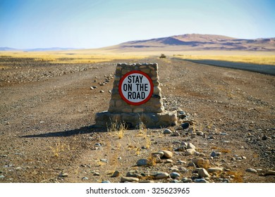 Road sign warning to stay on the road in Sossusvlei, with desert and straight road in the background Namibia (Selective focus)
