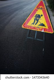 Road sign of works in progress for the reconstruction of the road surface, with laying of the finished asphalt.