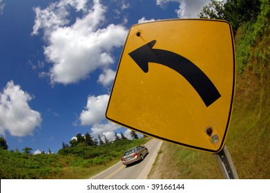 Road signal with a car going in the opposite direction