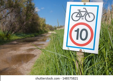A road with a signboard information about  limitation bicycle speed / A road with bicycle signboard information/ Aiguamolls de l'Empord� . Girona. Catalonia. Spain