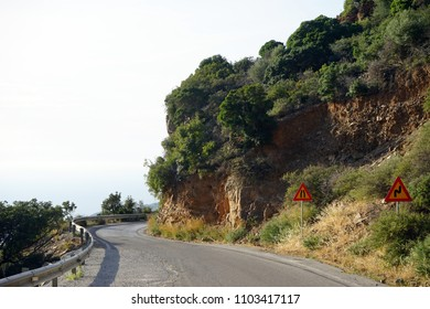 Road signs and asphalt road on the west coast of Crete, Greece