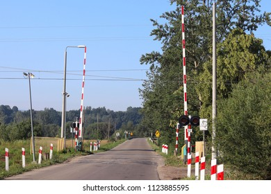 Road signs at the railway crossing with a barrier. Organization of the transport system of a European country. Red white coloring of anticipatory fog. Safety of traffic in road and rail transport.