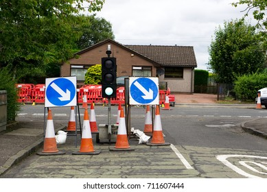 Road signs and roadworks partially blocking a road with traffic light and a suburban house in the background