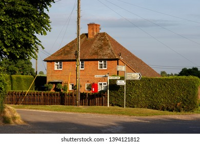 Road signs for villages from Malshanger with cottages and a red post box in the distance near Oakley Hampshire