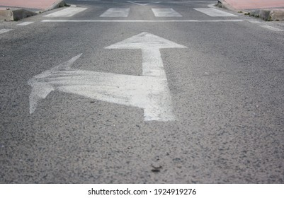 Road signs with white arrows indicating the direction of movement, straight ahead and turn, next to a zebra crossing and a yield point.