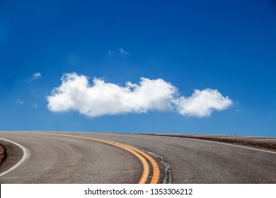 Road to the sky - Curve of blacktop road with yellow stripes runs around mountain and all you can see is a very blue sky and a fluffy white cloud - Pikes Peak