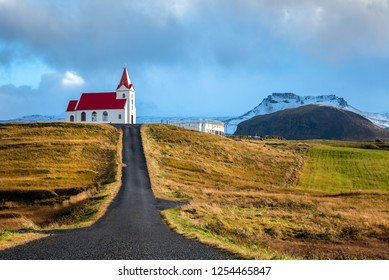 Road to a Small White Church with Red Roof on the Top of a Hill. Cloudy Mountains are in Background. Countryside of Iceland on a Sunny Autumn Day.