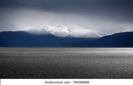 Road and snowcapped mountain, side view. Panoramic landscape