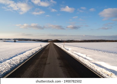 Road in snowy landscpape with awesome blue cloudy sky