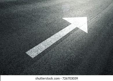 Road straight forward arrow direction sign on the sunny asphalt road ground.