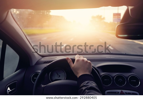 The road to success - a driver traveling on a road to the sun