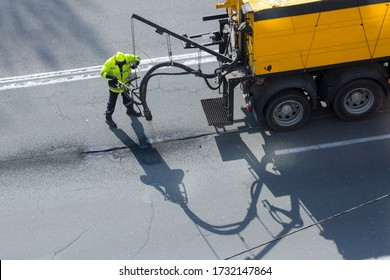 Road surface restoration work. The worker performs on road patcher work on the repair of cracks by filling and sealing with coated by bitumen emulsion and dry aggregate in the asphalt surface.