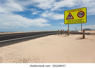 Road surrounded by desert and with the danger sign by it.