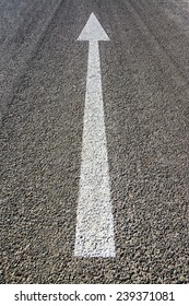 Road texture, white  one way sign, on poor quality asphalt.