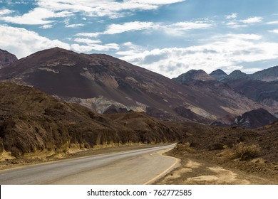The road that goes away past the stone hills, the Death Valley National Park, California, USA.