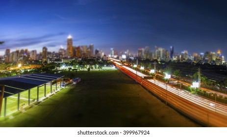 Road through the Bangkok city business area in the evening blue sky, tilt-shift effect background
