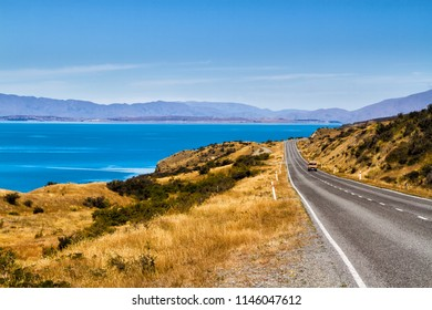 Road through beautiful and natural landscape of wild, pristine New Zealand countryside. View of lake Pukaki near Mount Cook or Aoraki.