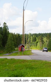 Road through the forest with car and mailboxes in a summer day