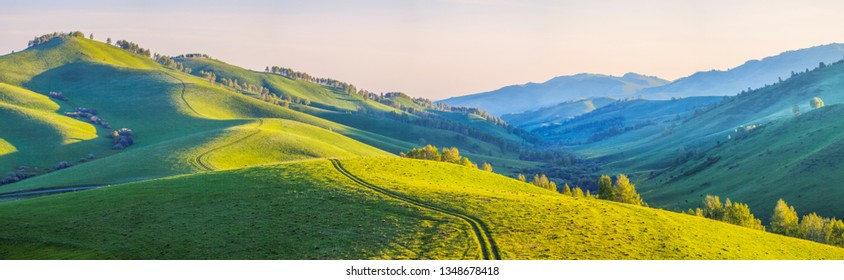 Road through green hills. Meadows and mountain slopes in the morning light. Spring rural landscape. Scenic panoramic view.
