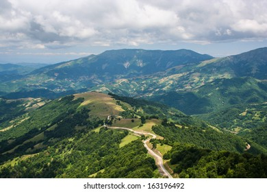 Road through high mountain range. Areal view on road going on top of the hill through high mountains with green forests on sides and dramatic rainy gray clouds in the sky.