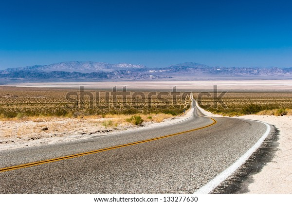 Road through the Mojave Desert, the Bristol Mountains and the Bristol Dry Lake in the back.